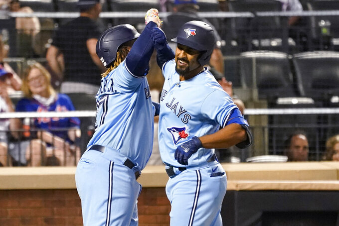 Toronto Blue Jays' Marcus Semien and Vladimir Guerrero Jr. (27) celebrate after scoring on a three-run home run by Semien during the fifth inning of the team's baseball game against the New York Mets, Saturday, July 24, 2021, in New York. (AP Photo/Mary Altaffer)