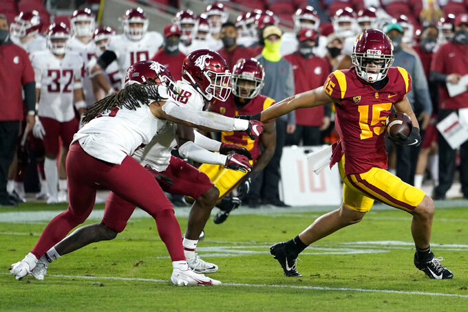 Southern California wide receiver Drake London, right, runs away from Washington State linebacker Jahad Woods, left, and defensive back George Hicks III (18) after a catch during the first half of an NCAA college football game in Los Angeles, Sunday, Dec. 6, 2020. (AP Photo/Alex Gallardo)