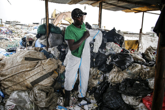 Isaac Kivai, who scavenges recyclables for a living, puts on a protective suit found in the trash at Dandora, the largest garbage dump in the Kenyan capital of Nairobi, Sunday, March 28, 2021. Trash pickers, who are not eligible for a COVID-19 vaccine shot, say the gear especially protects them from the weather during the rainy season. (AP Photo/Brian Inganga)