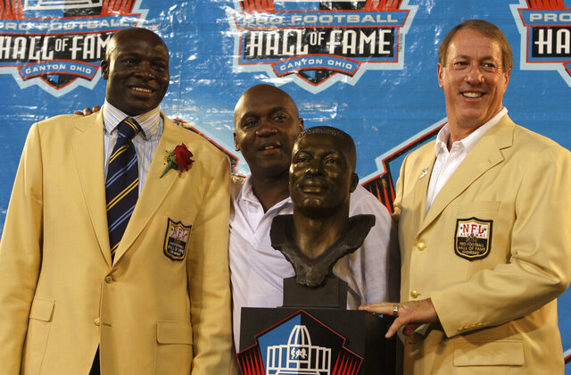 FILE - In this Aug. 8, 2009, file photo, from left Bruce Smith, Thurman Thomas, and Jim Kelly pose during Pro Football Hall of Fame induction ceremonies at the Pro Football Hall of Fame in Canton, Ohio. Jim Kelly and Bruce Smith formed the core of the Buffalo teams that made —- and lost — four consecutive Super Bowl appearances in the early 1990s. Kelly, who holds most every Bills passing record, was selected 14th in 1983. Smith, who holds the NFL record for most sacks, went No. 1 two years later.  (AP Photo/Tony Dejak, File)