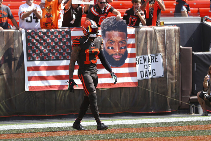 Cleveland Browns wide receiver Odell Beckham (13) stands in front of a fan holding a sign of his portrait prior to an NFL game against the Tennessee Titans, Sunday, Sept. 8, 2019, in Cleveland. (Margaret Bowles via AP)