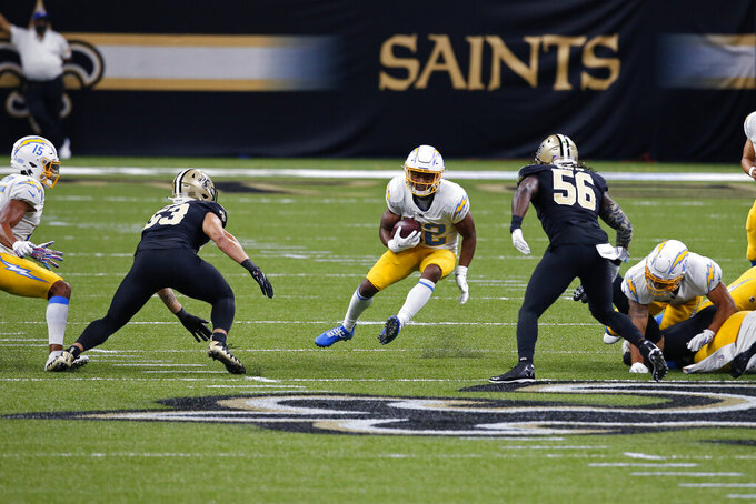 Los Angeles Chargers running back Justin Jackson carries against New Orleans Saints outside linebacker Demario Davis (56) and linebacker Zack Baun (53) in the first half of an NFL football game in New Orleans, Monday, Oct. 12, 2020. (AP Photo/Butch Dill)