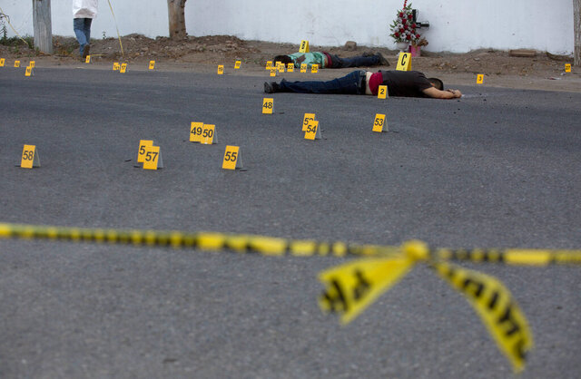FILE - In this June 29, 2017 file photo, investigators mark the spot where spent bullet casing fell next several bodies lying on a road in the town of Navolato, Sinaloa state, Mexico. For people in Mexican towns and villages where criminal gangs, armed groups and drug traffickers hold more sway than the state, the novel coronavirus is just the latest danger. The threat of death and the inability to move freely are nothing new. (AP Photo/Enric Marti, File)