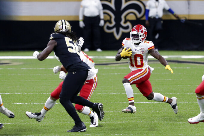 CORRECTS DATE Kansas City Chiefs wide receiver Tyreek Hill (10) carries against New Orleans Saints outside linebacker Demario Davis (56) in the first half of an NFL football game in New Orleans, Sunday, Dec. 20, 2020. (AP Photo/Butch Dill)