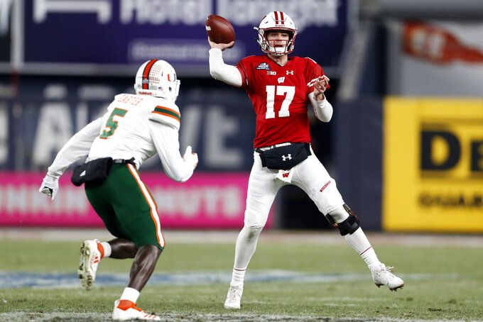 Wisconsin quarterback Jack Coan (17) passes under pressure from Miami defensive back Amari Carter during the first half of the Pinstripe Bowl NCAA college football game Thursday, Dec. 27, 2018, in New York. (AP Photo/Adam Hunger)