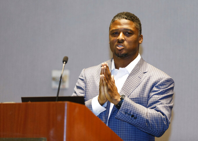 """FILE - Former NFL player Warrick Dunn speaks at the """"Beyond the Physical: A Symposium on Mental Health in Sports"""" hosted by the NFL, NFL Players Association and Cigna at Georgia Tech Hotel and Conference Center in Atlanta, in this Monday, May 14, 2018, file photo. Former NFL star Warrick Dunn is hosting a conversation centered on diversity and inclusion as part of his charity's Juneteenth celebration. Dunn, a three-time Pro Bowl running back with the Tampa Bay Buccaneers and Atlanta Falcons, will sit down with NFL Network host Steve Wyche on Thursday evening, June 10, 2021, for a virtual chat featuring guest appearances from various players past and present. (AP Photo/Todd Kirkland, File)"""