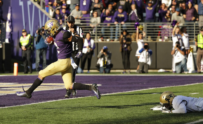 Washington wide receiver Aaron Fuller, left, scores a touchdown after evading Colorado cornerback Dante Wigleyk right, during the second half of an NCAA college football game, Saturday, Oct. 20, 2018, in Seattle. Washington won 27-13. (AP Photo/Ted S. Warren)