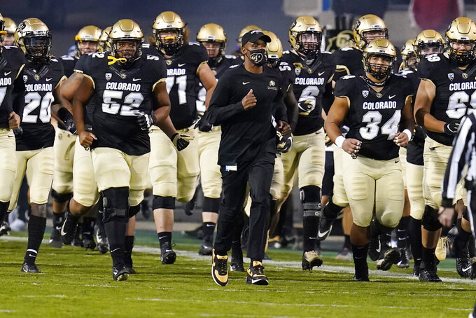 Colorado head coach Karl Dorrell, center, leads his players onto the gridiron to host UCLA in an NCAA college football game Saturday, Nov. 7, 2020, in Boulder, Colo. (AP Photo/David Zalubowski)