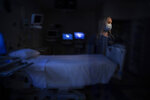 In this photo created with an in-camera multiple exposure, registered nurse Jamie Corcoran, part of a group of nurses who had been treating coronavirus patients in an intensive care unit, stands for a photo in the empty COVID-19 ICU at Providence Mission Hospital in Mission Viejo, Calif., Tuesday, April 6, 2021. As an ICU nurse the last five years, Corcoran got used to seeing death. She dealt with it by remaining detached. With COVID-19, detachment wasn't possible. (AP Photo/Jae C. Hong)