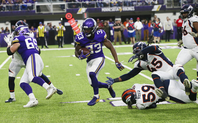 Minnesota Vikings running back Dalvin Cook (33) runs from Denver Broncos defenders Malik Reed (59) and A.J. Johnson (45) during the second half of an NFL football game, Sunday, Nov. 17, 2019, in Minneapolis. (AP Photo/Jim Mone)