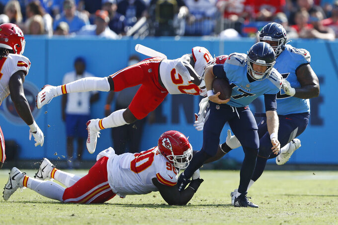 Tennessee Titans quarterback Ryan Tannehill (17) runs with the ball as Kansas City Chiefs defenders Jarran Reed (90) and Willie Gay (50) try to bring him down in the first half of an NFL football game Sunday, Oct. 24, 2021, in Nashville, Tenn. (AP Photo/Wade Payne)