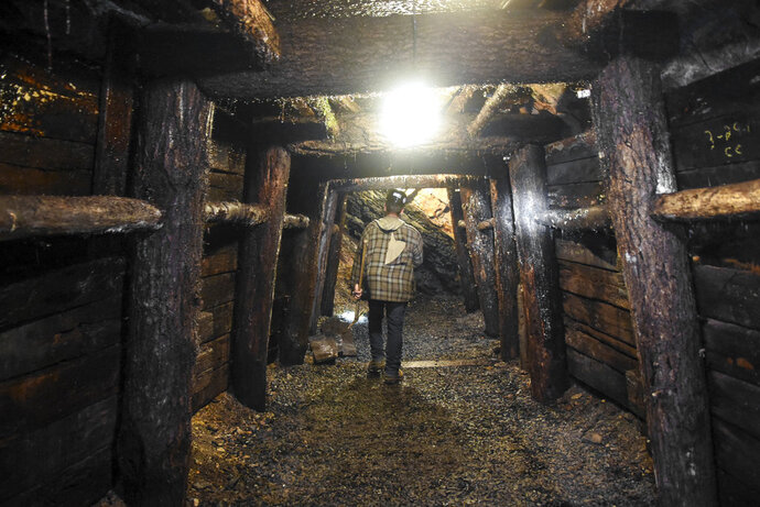 In this July 6, 2018, photo, Brad Purcell, certified mine foreman, walks through Pioneer Tunnel Coal Mine in Ashland, Pa., while showing his daily mandated inspection. The Pioneer Tunnel Coal Mine & Steam Train tourist attraction will be offering a new tour called the Pre-Shift Experience. It will allow the public to view and assist certified mine foreman Purcell with the daily examination to ensure the mine tunnel is safe for public entry. (Jacqueline Dormer/Republican-Herald via AP)