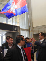 Cambodia's most prominent opposition politician Sam Rainsy greets supporters with the national flag as he attempted to return to Cambodia Thursday, Nov. 7, 2019 at Charles de Gaulle airport, north of Paris. Cambodia's main opposition figure Sam Rainsy said he was turned away from boarding a Thai Airways flight from Paris-Bangkok in his attempt to return to Cambodia from his self-imposed exile to challenge the longtime leader there. (AP Photo/Michel Euler)
