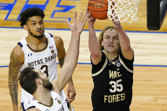Wake Forest guard Carter Whitt (35) grabs a rebound in front of Notre Dame guard Nikola Djogo, left, and teammate guard Prentiss Hubb (3) during the first half of an NCAA college basketball game in the first round of the Atlantic Coast Conference tournament in Greensboro, N.C., Tuesday, March 9, 2021. (AP Photo/Gerry Broome)