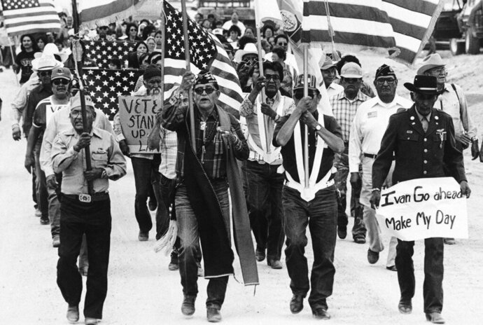 In this July 8, 1986, file photo, World War II Navajo veterans and supporters march through the reservation in a show of solidarity against giving up any of their land to the Hopis in Arizona.