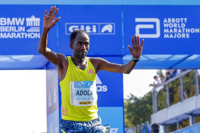 Ethiopia's Guye Adola celebrates after winning the Berlin Marathon in Berlin, Germany, Sunday, Sept. 26, 2021. (AP Photo/Lisa Leutner)