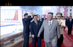 In this image made from video broadcasted by North Korea's KRT, North Korean leader Kim Jong Un, center, smiles as he leaves a ceremony to celebrate the 75th anniversary of the country's ruling party in Pyongyang Saturday, Oct. 10, 2020.(KRT via AP)