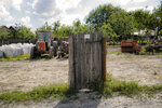 In this picture taken Tuesday, May 21, 2019, an old gate still stands outside a parking area for agricultural equipment in Luncavita, Romania. The Romanian village of Luncavita has benefited greatly from millions in development funds from the European Union, but few of its residents bothered to vote in previous European Parliamentary elections. (AP Photo/Vadim Ghirda)