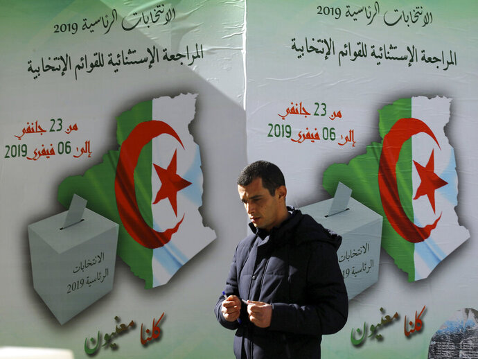 In this Feb. 5, 2019, photo, a man walks past a poster asking citizen to register to vote in Algiers. More than 180 people want to run for president of Algeria in the April election, amid growing uncertainty about whether President Abdelaziz Bouteflika, infirm following a stroke, is fit for yet another term after 20 years in charge of this gas-rich North African nation. (AP Photo/Anis Belghoul)