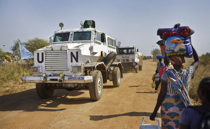 FILE - In this Monday, Dec. 30, 2013 file photo, a United Nations armored vehicle passes displaced people walking towards the U.N. Protection of Civilians camp in Malakal, South Sudan. The United Nations peacekeeping mission in South Sudan said on Friday, Sept. 4, 2020 that it has begun withdrawing its troops and police from the protection of civilians camps that continue to shelter more than 180,000 people two years after the end of the country's civil war. (AP Photo/Ben Curtis, File)