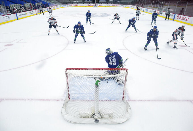 Edmonton Oilers' Connor McDavid, far right, scores against Vancouver Canucks goalie Braden Holtby (49) during the second period of an NHL hockey game, Monday, May 3, 2021, in Vancouver, British Columbia. (Darryl Dyck/The Canadian Press via AP)
