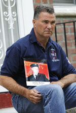 "FILE - In this May 3, 2012, file photo, Jim Riches, a retired New York deputy fire chief who responded to the 2001 terror attacks and lost his son, Jimmy, a fellow firefighter, poses for a photo with a photo of his son near his home in New York. Sept. 11 victims' relatives are greeting the news of President Donald Trump's now-canceled plan for secret talks with Afghanistan's Taliban insurgents with mixed feelings. ""I don't want to see other families suffer the way I did. That's the bottom line. Not soldiers or innocent victims of terrorism,"" Riches said. (AP Photo/Seth Wenig, File)"