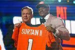 Alabama cornerback Patrick Surtain II, right, holds a team jersey with NFL Commissioner Roger Goodell after he was chosen by the Denver Broncos with the ninth pick in the NFL football draft, Thursday, April 29, 2021, in Cleveland. (AP Photo/Tony Dejak)