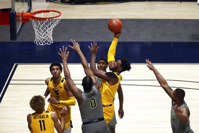 West Virginia forward Derek Culver (1) shoots while defended by Baylor forward Flo Thamba (0) and guard Jared Butler (12) during the first half of an NCAA college basketball game Tuesday, March 2, 2021, in Morgantown, W.Va. (AP Photo/Kathleen Batten)