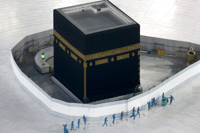"""FILE - In this March 7, 2020, file photo, workers disinfect the ground around the Kaaba, the cubic building at the Grand Mosque, in the Muslim holy city of Mecca, Saudi Arabia, which emptied Islam's holiest site for what they say sterilization over fears of the new coronavirus. The Islamic State group in an audio message released late Thursday, May 28, 2020, blasted Iraq's new prime minister, calling him an """"American agent"""" and criticizing the closure of Islam's holiest shrine in the Saudi holy city of Mecca to limit the spread of coronavirus. (AP Photo/Amr Nabil, File)"""