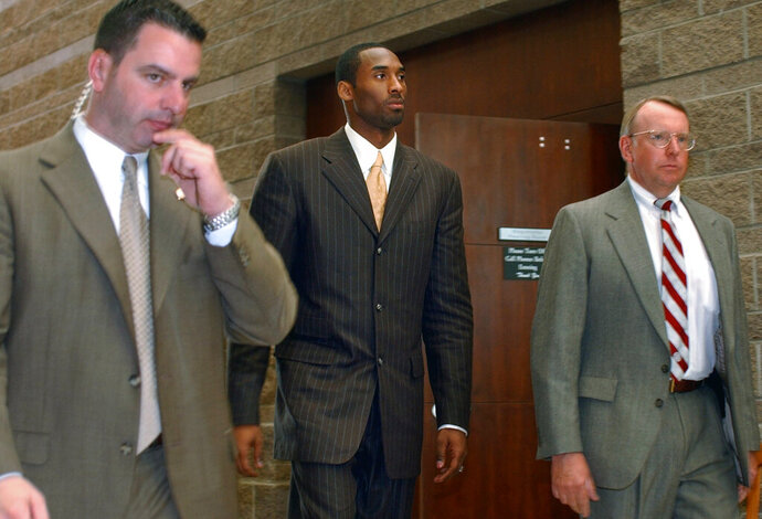 FILE - In this Wednesday, March 24, 2004, file photo, Los Angeles Lakers' Kobe Bryant, center, walks out of a holding area as he prepares to leave for a lunch break from proceedings in his sexual assault case as members of his security team accompany him, in Eagle, Colo. Some argued that there was no need to dredge up accounts of the 2003 rape allegation against Bryant when he died suddenly Sunday, Jan. 26, 2020. Others viewed it as another example of an icon being given a pass because he was a successful athlete. (AP Photo/Ed Andrieski, File)