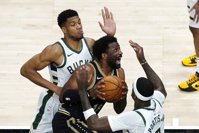 Atlanta Hawks forward Solomon Hill (18) drives between Milwaukee Bucks' Giannis Antetokounmpo, left, and Bobby Portis (9) during the first half of an NBA basketball game Thursday, April 15, 2021, in Atlanta. (AP Photo/John Bazemore)
