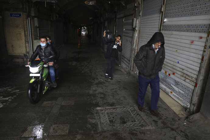 People leave the closed Tehran's Grand Bazaar, Iran's main business and trade hub, Satuday, Nov. 21, 2020. Iran on Saturday shuttered businesses and curtailed travel between its major cities, including the capital of Tehran, as it grapples with the worst outbreak of the coronavirus in the Mideast region. (AP Photo/Vahid Salemi)