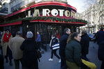 People walk past the restaurant La Rotonde, in Paris, Saturday, jan.18, 2020. The Paris prosecutor's office says it has opened an investigation to determine the causes of the Rotonde fire. (AP Photo/Thibault Camus)