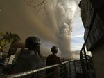 In this Jan. 12, 2020, photo, people watch plumes of smoke and ash rise from as Taal volcano erupts in Tagaytay, Cavite province, outside Manila, Philippines. (AP Photo/Aaron Favila, File)