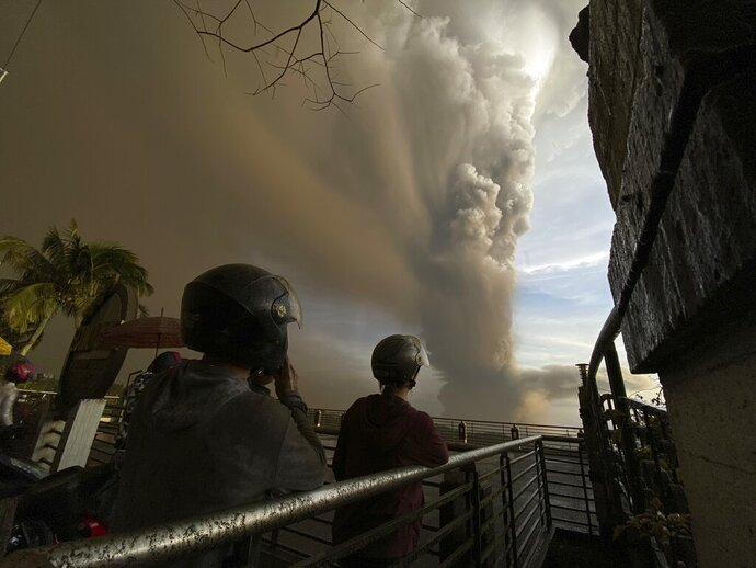In this Jan. 12, 2020, photo, people watch plumes of smoke and ash rise from as Taal volcano erupts in Tagaytay, Cavite province, outside Manila, Philippines. (AP Photo/Aaron Favila)