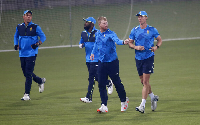 South Africa Twenty20 team's skipper Heinrich Klaasen, second right, with teammates warm up during a practice session for upcoming Twenty20 match against Pakistan, at the Gaddafi Stadium, in Lahore, Pakistan, Tuesday, Feb. 9, 2021. South Africa will play three Twenty20 matches against Pakistan, starting from Feb. 11. (AP Photo/K.M. Chaudary)