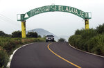 In this Oct. 16, 2019 photo, a sign arches over a two lane road welcoming vistors to El Aguaje, Mexico. Michoacan state police did make a rare appearance in El Aguaje last Monday, Oct. 14, they were ambushed and slaughtered by Jalisco cartel gunmen.  (AP Photo/Marco Ugarte)