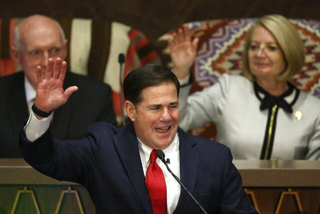 Arizona Republican Gov. Doug Ducey, front, raises his arm as he makes a pledge as he speaks during his State of the State address about Arizona's economy, new jobs, prison reform, and education as Senate president Karen Fann, R-Prescott, back right, and House Speaker Rusty Bowers, R-Mesa, back left, listen in on the opening day of the legislative session at the Capitol, Monday, Jan. 13, 2020, in Phoenix. (AP Photo/Ross D. Franklin)
