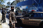 Military police stand guard by a bus carrying Argentina's Boca Juniors soccer team which is parked outside a police station in Belo Horizonte, Brazil, Wednesday, July 21, 2021, the morning after the team was eliminated from the Copa Libertadores tournament which ended in a brawl and destruction in the locker room. (AP Photo/Bruna Prado)