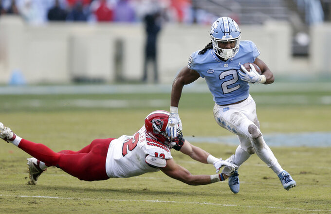 North Carolina State's Brock Miller (12) dives for North Carolina's Jordon Brown (2) during the first half of an NCAA college football game in Chapel Hill, N.C., Saturday, Nov. 24, 2018. (AP Photo/Gerry Broome)