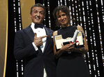 Director Mati Diop, right, holds the grand prix Palme d'Or award for the film 'Atlantique' presented by actor Sylvester Stallone during the awards ceremony at the 72nd international film festival, Cannes, southern France, Saturday, May 25, 2019. (Photo by Vianney Le Caer/Invision/AP)