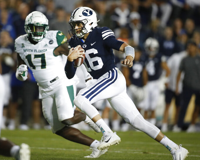 BYU quarterback Baylor Romney (16) runs the ball as South Florida defensive tackle Blake Green (17) looks on in the first half of an NCAA college football game Saturday, Sept. 25, 2021, in Provo, Utah. (AP Photo/George Frey)