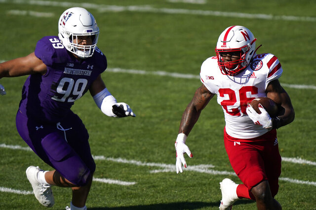 Nebraska running back Dedrick Mills, right, runs past Northwestern defensive end Earnest Brown IV, during the first half of an NCAA college football game in Evanston, Ill., Saturday, Nov. 7, 2020. (AP Photo/Nam Y. Huh)
