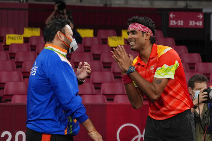 India's Kamal Achanta speaks to his coach after winning the table tennis men's singles second round match against Portugal's Tiago Apolonia at the 2020 Summer Olympics, Monday, July 26, 2021, in Tokyo. (AP Photo/Kin Cheung)