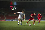 In this photo provided by the Korea Football Association, South Korea's Hwang Hee-chan, left, fights for the ball against North Korea's Kim Chol Bom during their Asian zone Group H qualifying soccer match for the 2022 World Cup at Kim Il Sung Stadium in Pyongyang, North Korea, Tuesday, Oct. 15, 2019. (The Korea Football Association via AP)