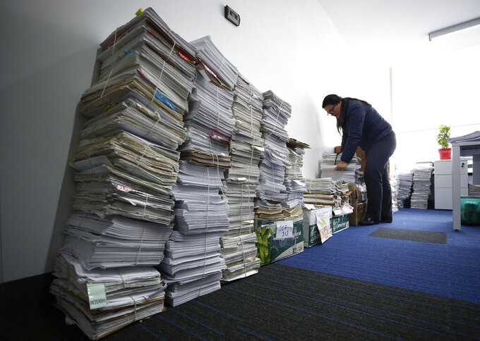 FILE - In this Dec. 14, 2018 file photo, a clerk goes over court files at the headquarter of the Special Peace Jurisdiction in Bogota, Colombia. The South American country's postwar reconciliation tribunal said Monday, April 19, 2021, that violence against former guerrilla fighters and community leaders is increasing in rural areas and jeopardizing its attempts to investigate crimes that took place during six decades of conflict that killed an estimated 260,000 people and forced millions to flee their homes. (AP Photo/Fernando Vergara, File)