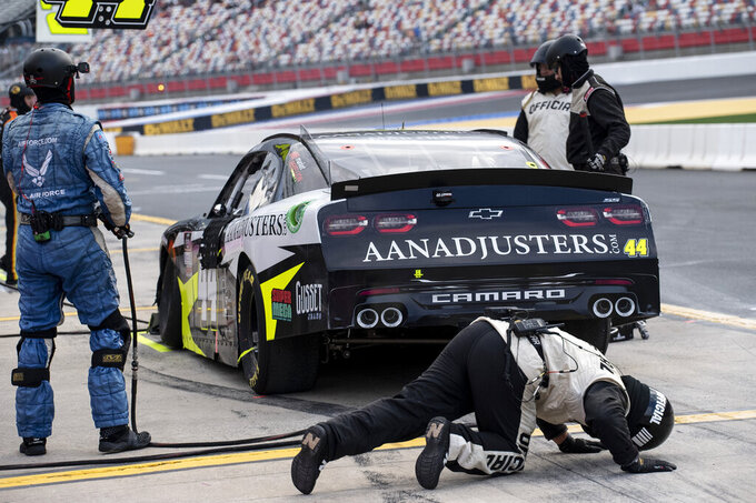 A NASCAR official checks under NASCAR Xfinity Series driver Tommy Joe Martins (44) car on pit road after a crash during the NASCAR Xfinity auto racing race at the Charlotte Motor Speedway Saturday, Oct. 9, 2021, in Concord, N.C. (AP Photo/Matt Kelley)