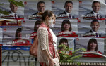 Two women walk past campaign posters of the ruling SDSM party in Skopje, North Macedonia on Thursday, July 16, 2020, a day after the country's parliamentary elections. The pro-Western SDSM party in North Macedonia is poised to try to form a coalition government following a narrow election victory. (AP Photo/Boris Grdanoski)