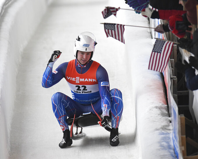 FILE - Tucker West, of the United States, celebrates his second place finish after his second run of a men's World Cup luge event in Lake Placid, N.Y., in this Sunday, Dec. 1, 2019, file photo. Luge's governing body took upcoming World Cup races away from the U.S. and Canada on Tuesday, Aug. 31, 2021, citing ongoing difficulties in getting foreign athletes into and out of the North American countries during the pandemic. The planned World Cup stops in Whistler, British Columbia, and Lake Placid, New York, will now both be held at the 2014 Sochi Olympic track in Krasnaya Polyana, Russia.(AP Photo/Hans Pennink, File)