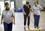 Dance instructor, Jessica Kehn center, works with Trisha Gump, an inmate at Ohio Reformatory for Women, during the first of 12 tap dance classes, part of the Tapestry Program, Friday, September 6, 2019. (Courtney Hergesheimer/The Columbus Dispatch via AP)